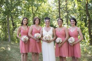 Image of bride and bridal party wearing rose color dresses in garden