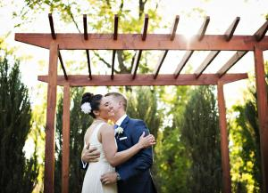 Image of a bride and groom kissing under garden trellis