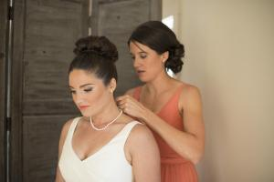 Image of maid of honor putting pearls on a natural bride