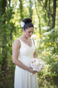 Image of summer bride gazing at bouquet in garden