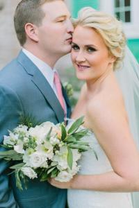 Image of a groom softly kissing his naturally beautiful bride