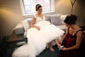 Image of a vintage glam winter bride sitting on sofa at Renaissance hotel Albany New York bridesmaid is putting her shoes on