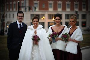 Image of winter bride and her bridesmaids wearing fur holding cranberry bouquet