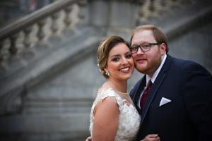 Image of smiling bride and groom outside during winter in front of the Capital Building Albany New York