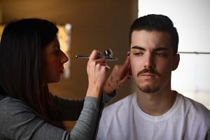 Image of makeup artist Jessica Lafata applying airbrush foundation to male