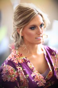 Image of bridesmaid wearing purple floral robe showing off a dramatic makeup look