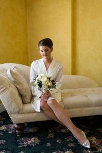 Image of bride in her robe sitting on chaise holding her bouquet