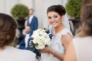 Image of excited spring bride holding bouquet wearing lace dress