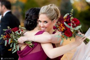 Image of a blonde bridesmaid embracing her friend each holding a crimson fall bouquet of flowers