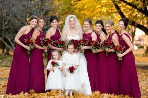 Image of fall bride with her bridesmaids and two flower girls fall foliage in the background