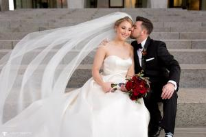 Image of a fall bride with her groom in front of the New York State Museum groom is kissing brides cheek veil is blowing in the wind