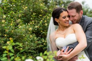 Image of groom embracing bride outside in garden