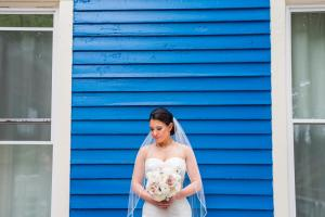 Image of a bride looking down bright blue house in background