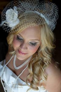 Image of a glam bride with pearls and birdcage veil showing  off makeup at the whiteface lodge in lake placid