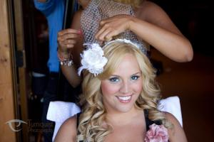 Image of smiling bride while makeup artist applies makeup