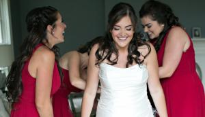 Image of bridesmaids helping a happy bride get into her wedding dress