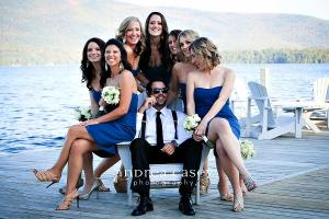 Image of a groom sitting in chair on a dock in Lake George New York bridesmaids sitting around him lauging