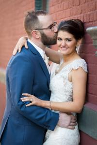 Image of groom in soft blue tux embracing his sweet bride with a soft kiss
