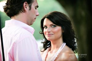Image of engagement shoot woman is smiling with dark hair and flawless skin man is looking down at her