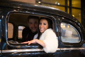 Image of bride and groom in vintage car bride is wearing white fur and smiling