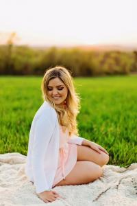 Image of happy woman sitting on blanket in grassy field for engagement photo shoot