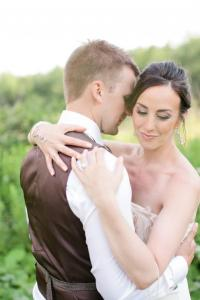 Image of summer bride and groom embracing one another at black feather farm